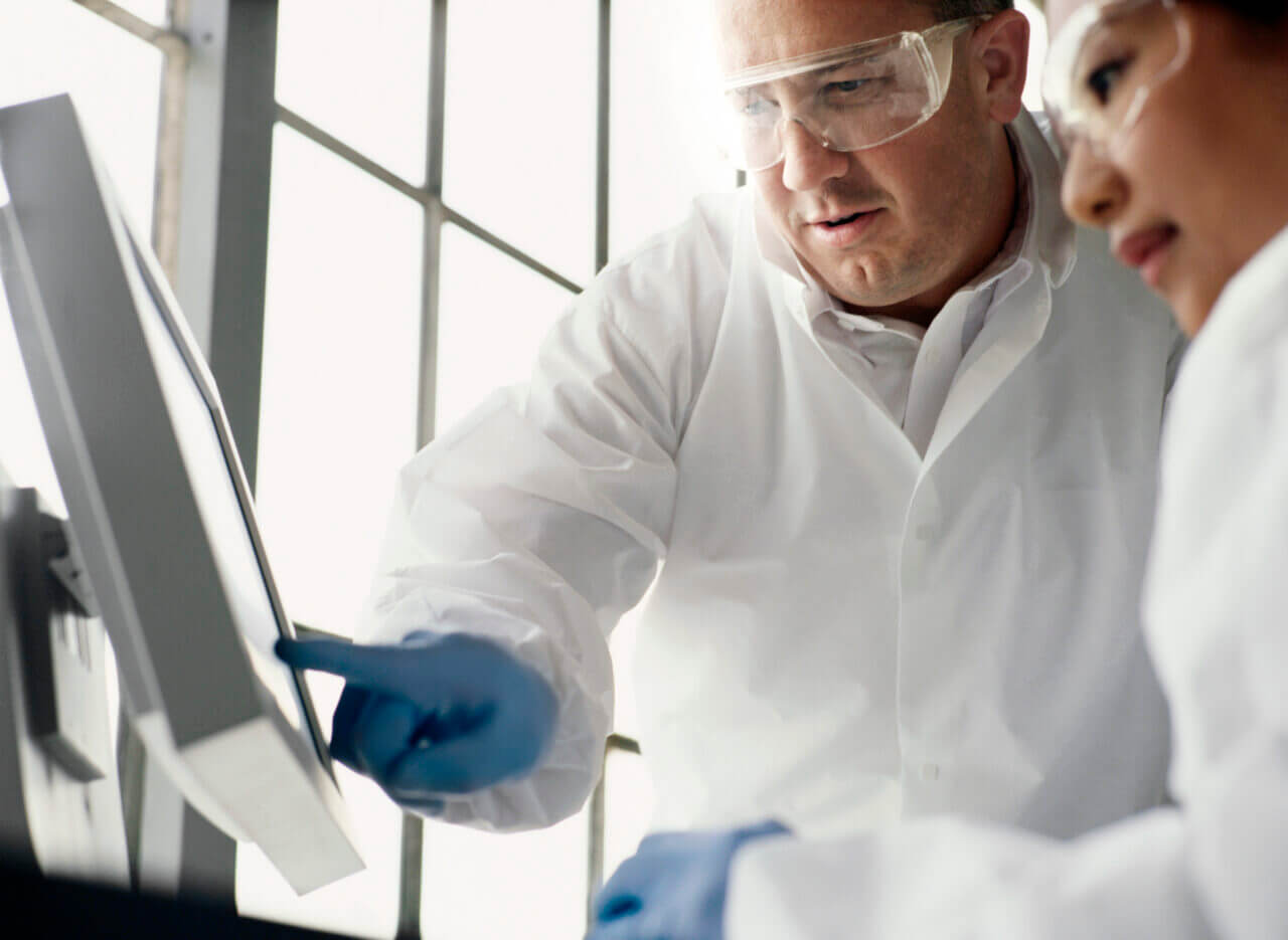Two lab technicians examining data on computer screen, low angle view