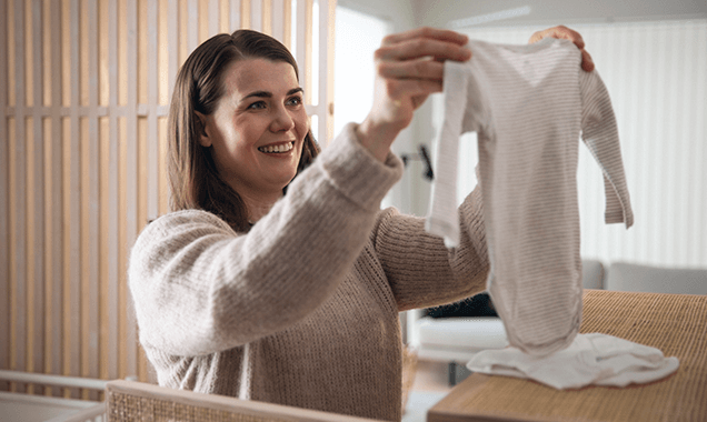 Woman Holding Baby Clothes
